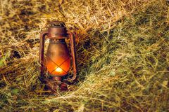 Vintage lit lamp in hay. Close view Stock Photo