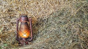 Vintage lit lamp in hay. Vintage lit lamp in hay, close view Stock Photography