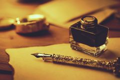 Vintage literature - retro feather pen and inkwell on old parchment. Paper stock photography