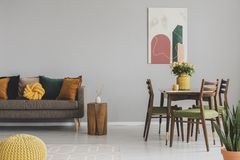 Vintage living and dining room interior with retro table with chairs and comfortable sofa with pillows stock photography