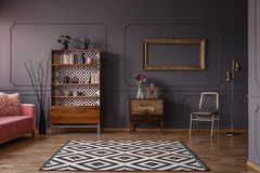 Vintage living room interior with a patterned rug, cupboard, golden frame on the wall, chair and wall molding royalty free stock image
