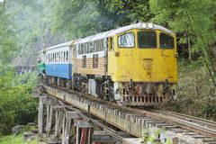 Vintage locomotive passes Death railway in Kanchanaburi, Thailand. Royalty Free Stock Image