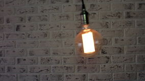 Vintage Loft lamp swinging on a brick wall stock video footage
