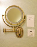 Vintage look brass adjustable wall mount magnifying mirror on half circle wallpaper. With shavers only socket and volume control next to it. This is a common royalty free stock images