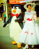 Vintage look of Mary Poppins escorted by a Penguin. Stock Photo