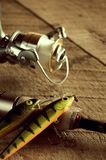 Vintage Looking Fishing Lures, Rod and Reel on Wood Table. Vertical Royalty Free Stock Images