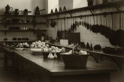 Antique XIX century old kitchen with tools, pans, pots and food ingredients. Vintage looking image of an antique XIX century old kitchen with tools, pans, pots royalty free stock images