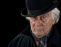 Old man wearing a bowler hat. Vintage looking old man with a black coat, gray scarf and black bowler hat staring straight at the camera isolated on black Stock Photo