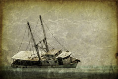 Vintage looking picture of a capsized fishing boat in the caribbean Royalty Free Stock Photography