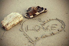 Vintage Looking Sepia Leather Sandal and Love Message in Sand Royalty Free Stock Photos