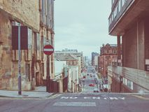 Vintage look Glasgow hill. Vintage looking Typical steep street in Glasgow city centre hills Royalty Free Stock Photos