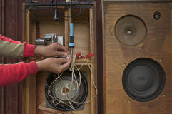 Vintage Loudspeakers Repair. Hands of a diy man busy with vintage loudspeakers repair, filtered image Royalty Free Stock Photography