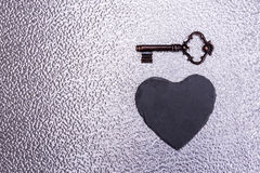 Vintage love hart key. Old key with heart on texture Stock Photos