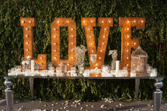Vintage love light bulb sign decoration for wedding valentine day. Over a table with candles Stock Photo