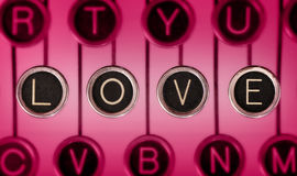 Vintage Love Stories. Close up of old typewriter keyboard with scratched chrome keys that spell out LOVE. Lighting and focus are centered on LOVE Stock Photo