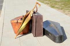 Vintage luggage items, suitcase, umbrella, hat box and musical instrument. Standing on a sidewalk in sunlight stock image