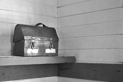 Vintage Lunch Pail. A black and white image of a vintage lunch pail placed on a wooden shelf stock photo