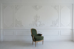 Vintage luxury green armchair in white room over wall design bas-relief stucco mouldings roccoco elements stock photography