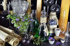 Vintage magic bottles and lilac flowers on witch table. Vintage bottles, scrolls, glassware, herbs and flowers on witch table. Halloween or esoteric concept. Old royalty free stock photography