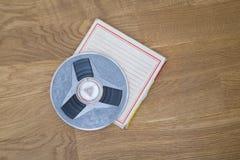 Vintage magnetic audio reel on the grunge wooden floor Stock Images