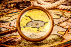 Vintage magnifying glass lies on the ancient map of the North Po Stock Photo