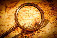Vintage magnifying glass lies on an ancient world map stock photography