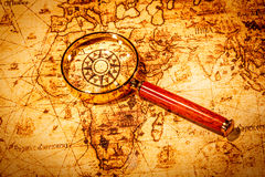 Vintage magnifying glass lies on an ancient world map Royalty Free Stock Photo