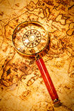 Vintage magnifying glass lies on an ancient world map Royalty Free Stock Photography