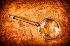 Vintage magnifying glass lies on an ancient world map Stock Photo