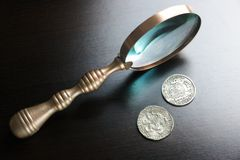 Vintage Magnifying Glass And Old Silver Coins On Black Table Stock Photos
