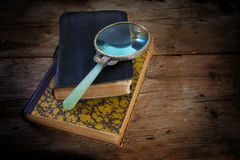 Vintage magnifying glass on two antique books, symbol for scienc Royalty Free Stock Image