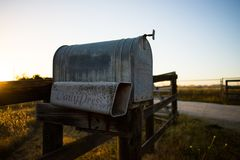 Vintage mailbox. A metal, vintage mailbox with a slot for newspaper. This was take on a field adjacent to a vineyard royalty free stock photography