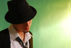 Vintage man 2. Latino male  In black vest stripped shirt on green wearing a vintage hat Royalty Free Stock Photos