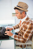 Vintage man in straw hat typing on typewriter Royalty Free Stock Image