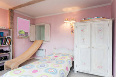Vintage mansion - girl's room. Vintage mansion - a pink girl's room with a slide, a bed and shelves Royalty Free Stock Photos