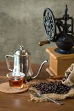 Vintage manual coffee grinder with coffee beans and cup.  Stock Photo
