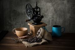 Vintage manual coffee grinder with coffee beans and cup.  Royalty Free Stock Photography