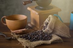 Vintage manual coffee grinder with coffee beans and cup.  Stock Images