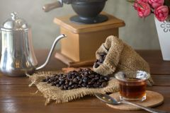 Vintage manual coffee grinder with coffee beans and cup.  Royalty Free Stock Photo