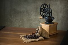 Vintage manual coffee grinder with coffee beans and cup.  Stock Photos