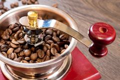 Vintage manual coffee grinder with coffee beans on on dark wood. Table Stock Image