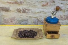 Vintage manual coffee grinder and coffee beans on old wooden table. Background - stone wall stock photos