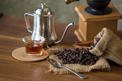 Vintage manual coffee grinder with coffee beans and cup.  Stock Photography