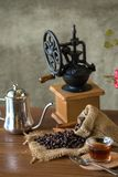 Vintage manual coffee grinder with coffee beans and cup.  Royalty Free Stock Images