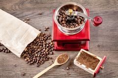 Vintage manual coffee grinder with coffee beans and with ground. Coffee on on dark wood table Royalty Free Stock Photo