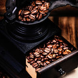 Vintage manual coffee grinder with coffee beans on wooden brown. Background closeup. Coffee Mill with roasted coffee grains Royalty Free Stock Images