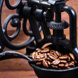 Vintage manual coffee grinder with coffee beans on wooden brown. Background macro. Coffee Mill with roasted coffee grains Royalty Free Stock Photography