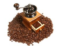 Vintage manual coffee grinder with coffee beans on wooden spoon. Isolated antique coffee grinder and coffee beans on wooden spoon Stock Photography