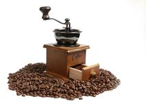 Vintage manual coffee grinder with coffee beans on wooden spoon. Isolated antique coffee grinder and coffee beans on wooden spoon Stock Image