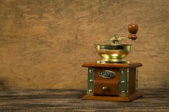 Vintage manual coffee grinder on wooden table with color wall background royalty free stock images